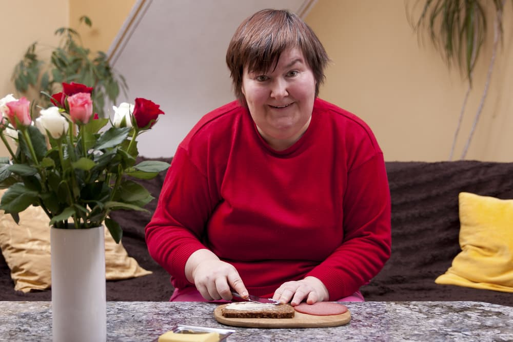 Handicapped woman is making up a sandwich